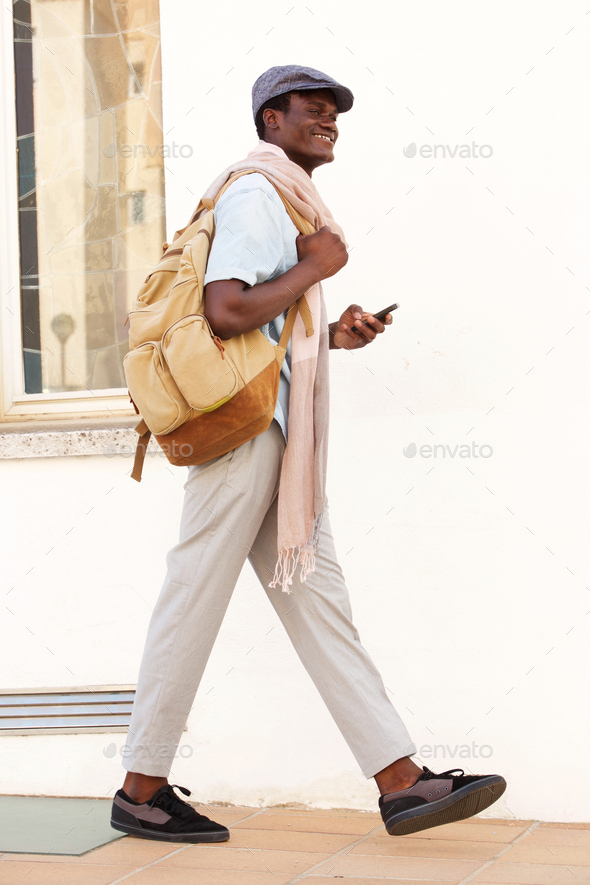 Full length handsome young guy walking with bag and phone - Stock Photo - Images