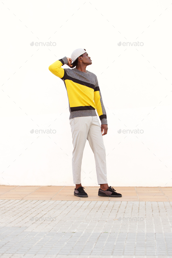 Full length stylish young african man standing outside and looking away - Stock Photo - Images