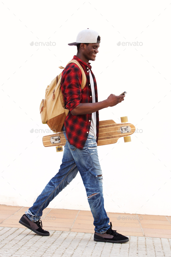 Side portrait of smiling African American student walking with skateboard and smart phone - Stock Photo - Images