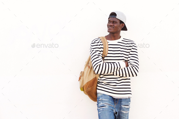 handsome young African American student leaning against wall - Stock Photo - Images
