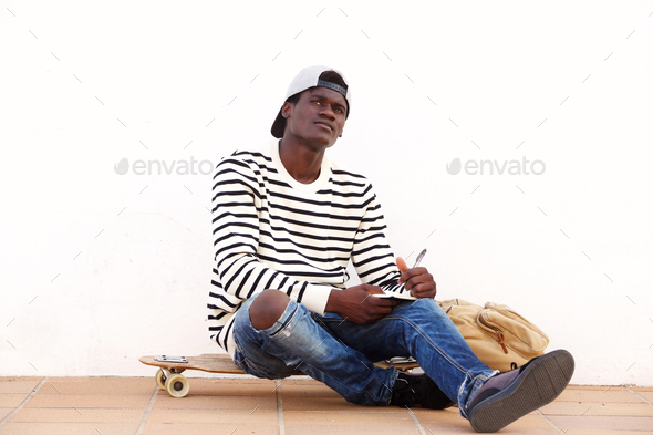 young african man sitting on skateboard outdoors with book - Stock Photo - Images