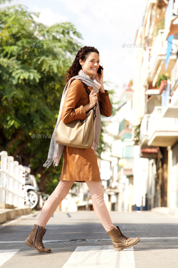 Full body young woman talking on mobile phone and crossing stree - Stock Photo - Images
