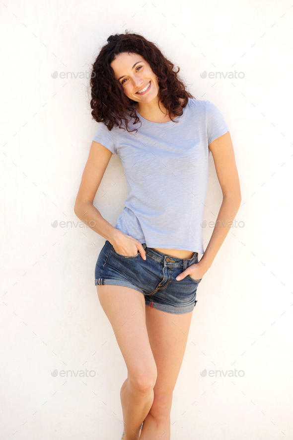 beautiful young woman in shorts smiling against white background - Stock Photo - Images