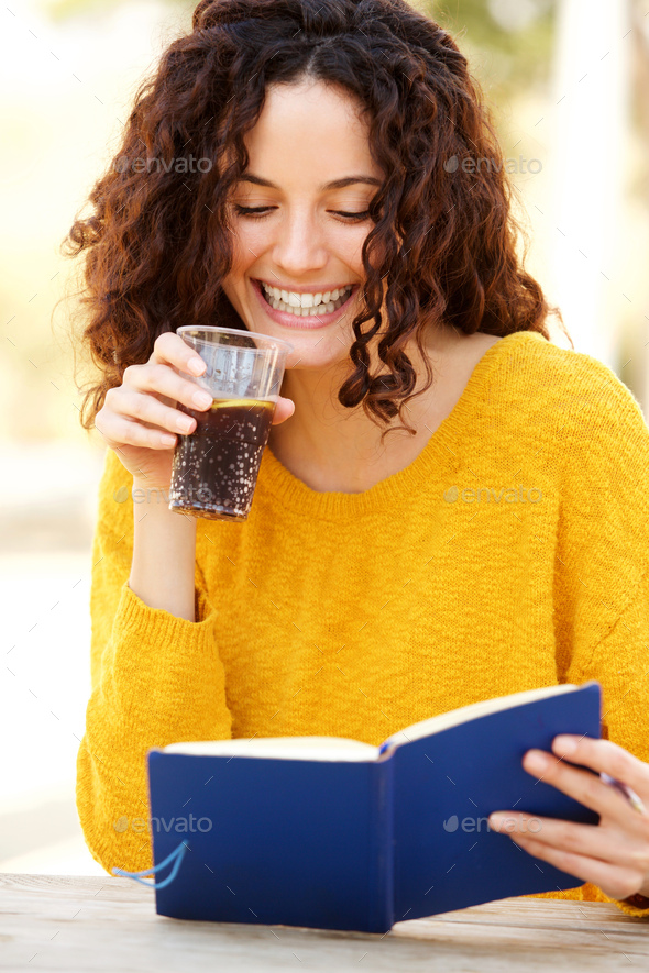 young woman reading book with a drink - Stock Photo - Images