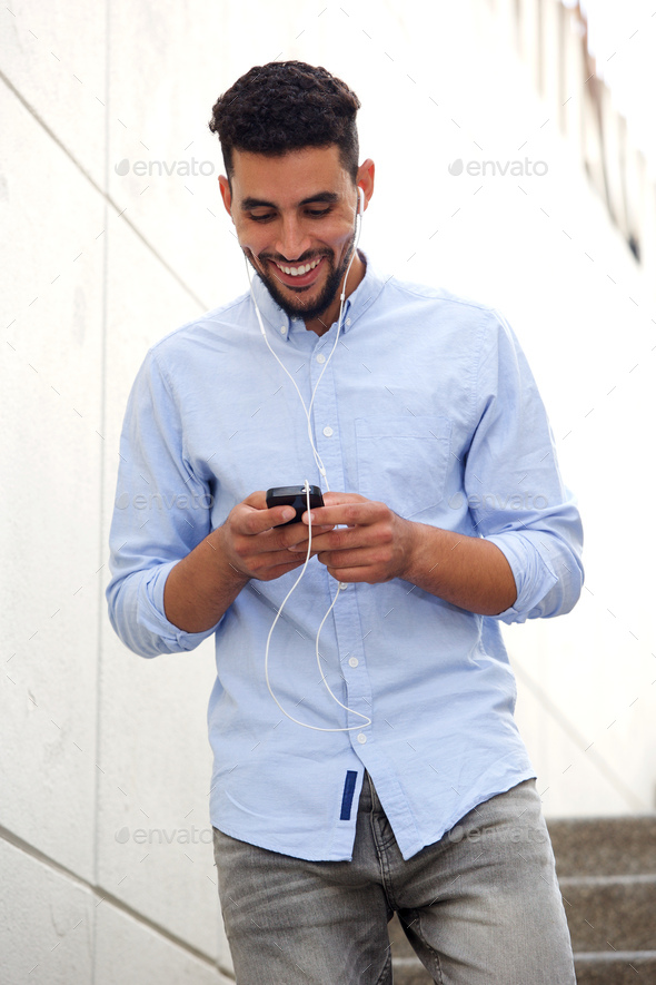 young man smiling and walking with mobile phone and earphones - Stock Photo - Images