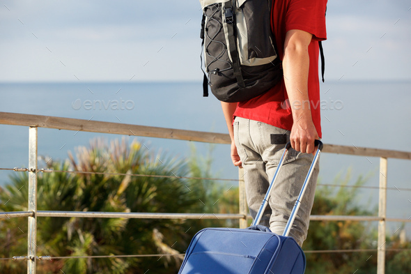 man traveling with backpack and pulling suitcase outside - Stock Photo - Images