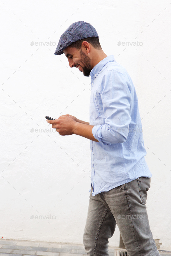 happy young North African man walking and looking at cellphone a - Stock Photo - Images