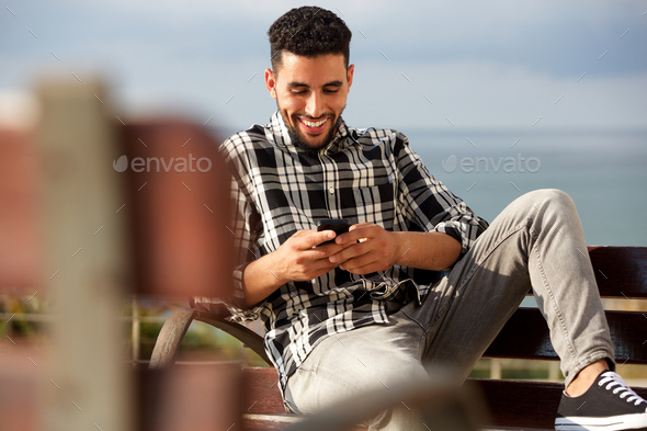 happy young arabic man sending text message on mobile phone - Stock Photo - Images