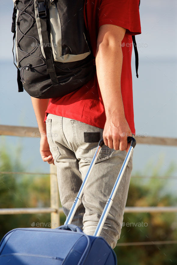 man walking with backpack and pulling suitcase - Stock Photo - Images