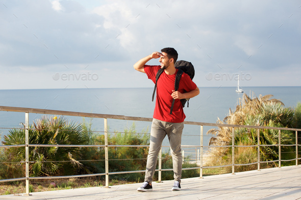 Full length happy young man walking with backpack by the sea - Stock Photo - Images