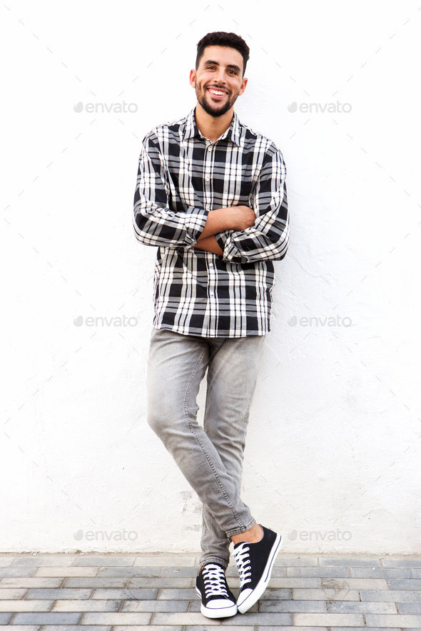 Full length young arabic man smiling against white background - Stock Photo - Images