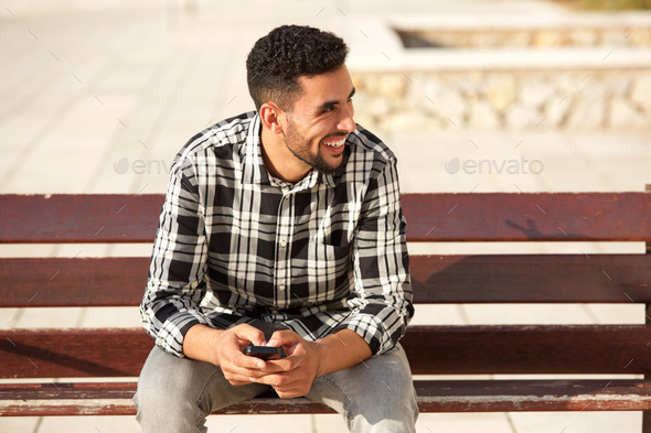 young arabic man smiling with cellphone outside - Stock Photo - Images