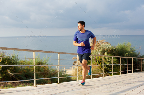 Full length healthy young man running outside with earphones - Stock Photo - Images