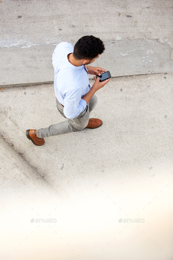 above of man walking and using cellphone outside - Stock Photo - Images