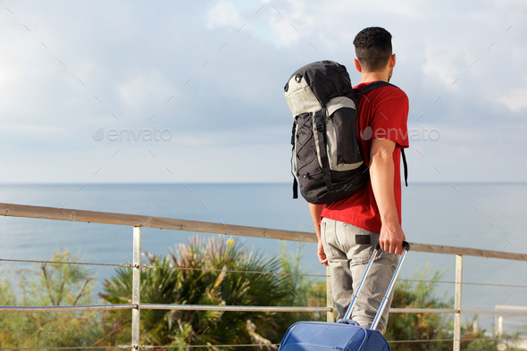 man traveling with backpack and suitcase - Stock Photo - Images