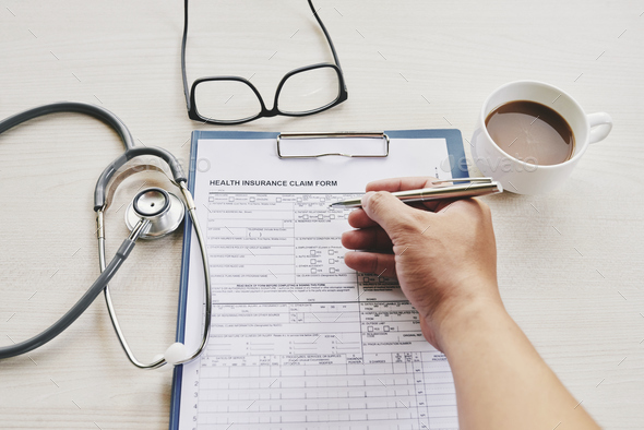 Patient filling healthy insurance document - Stock Photo - Images