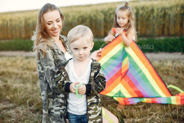 Mother with cute little children in a summer field - Stock Photo - Images