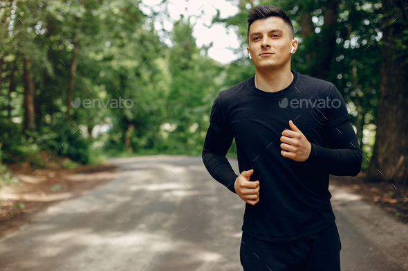 Sports man in a morning summer park - Stock Photo - Images