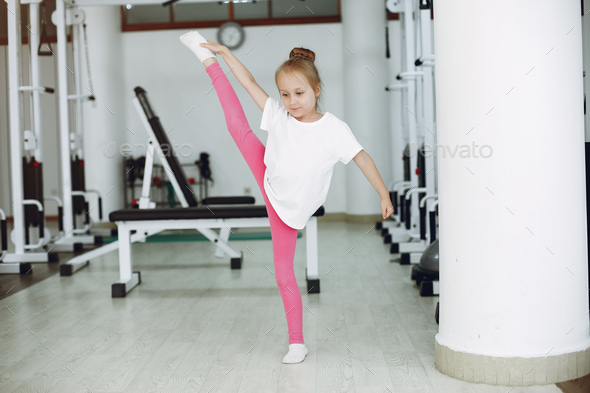 Cute little girl are engaged in gymnastics in the gym - Stock Photo - Images