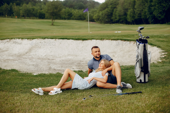 Beautiful couple playing golf on a golf course - Stock Photo - Images