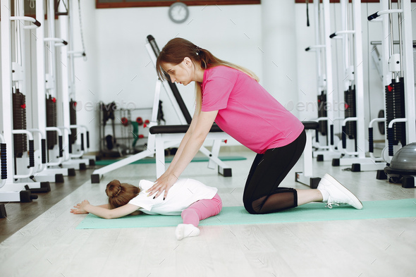 Mother with little daughter are engaged in gymnastics in the gym - Stock Photo - Images