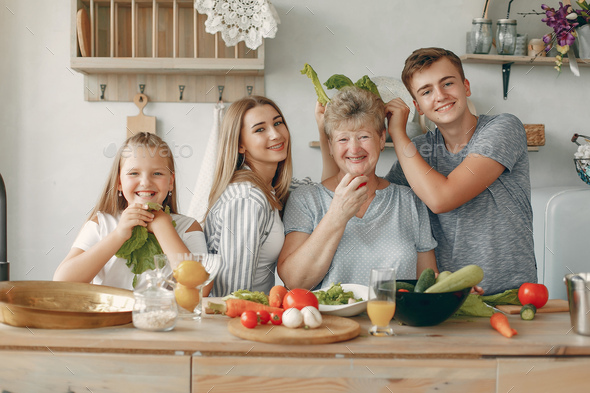 Beautiful big family prepare food in a kitchen - Stock Photo - Images