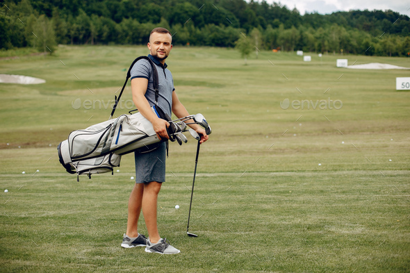 Handsome man playing golf on a golf course - Stock Photo - Images
