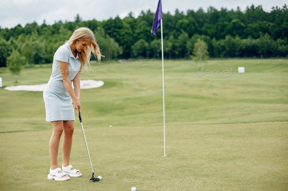 Beautiful girl playing golf on a golf course - Stock Photo - Images