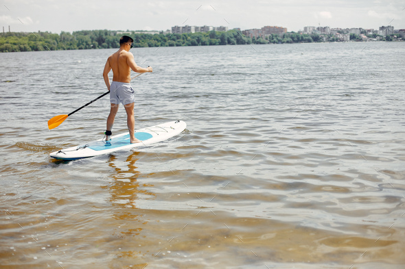 Sup surfer on a summer beach - Stock Photo - Images