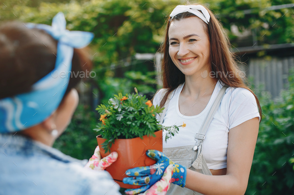 Beautiful women works in a garden near the house - Stock Photo - Images