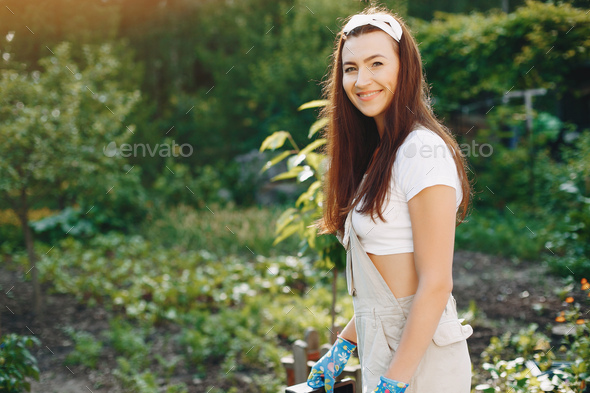 Beautiful woman works in a garden near the house - Stock Photo - Images