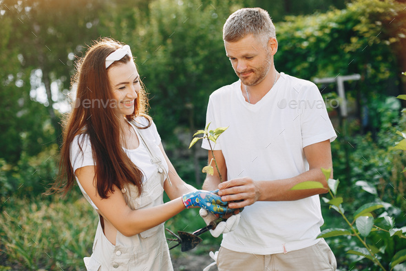 Beautiful couple works in a garden near the house - Stock Photo - Images