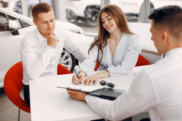Stylish and elegant couple in a car salon - Stock Photo - Images
