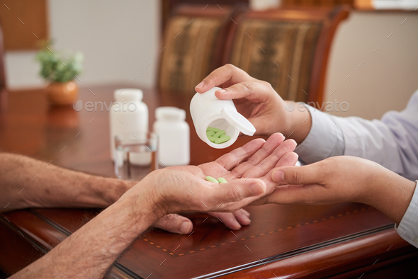 Crop doctor pouring pills in hand of patient - Stock Photo - Images