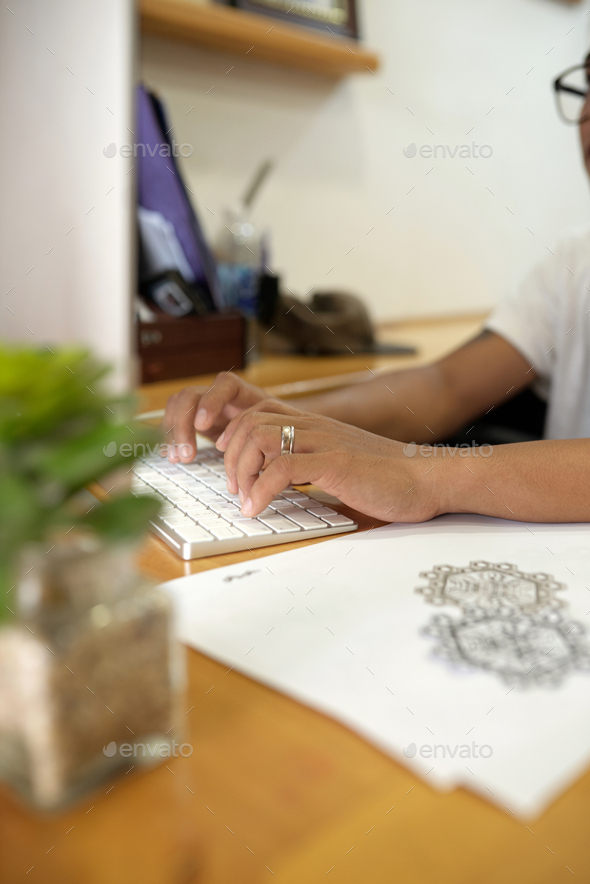 Tattoo master working on computer - Stock Photo - Images