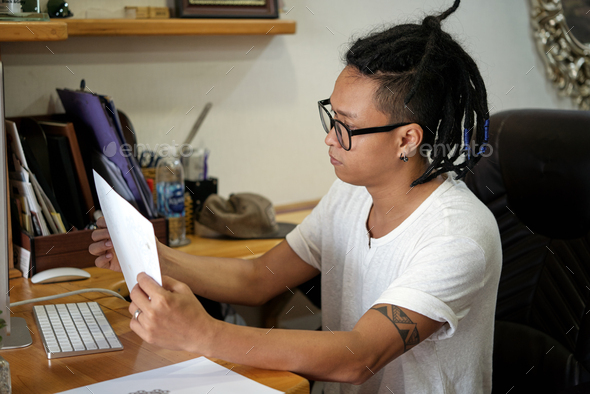 Master looking at tattoo sketch - Stock Photo - Images