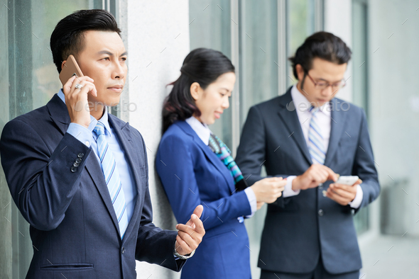 Young businesspeople with smartphones outdoors - Stock Photo - Images