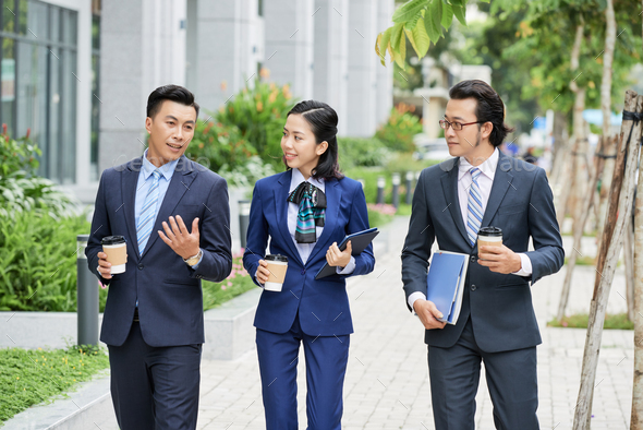 Modern businesspeople with coffee on street - Stock Photo - Images