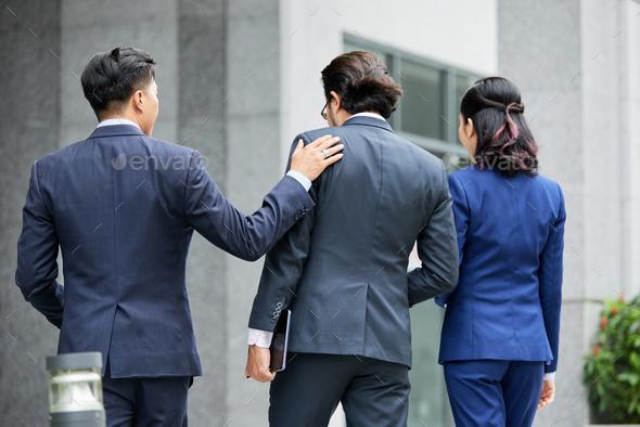 Group of elegant businesspeople walking on street - Stock Photo - Images