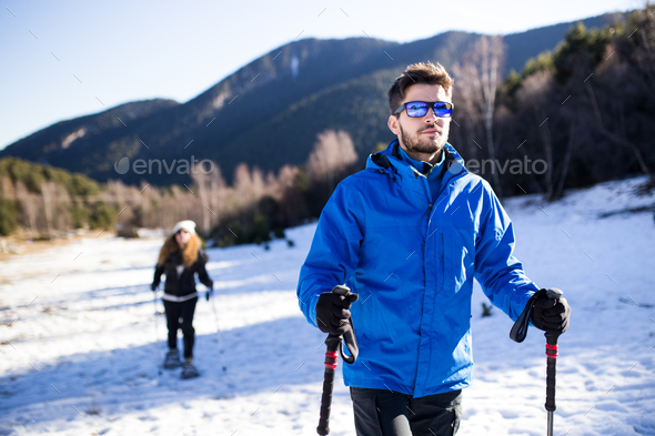 Young couple walking in snowshoes over winter background. - Stock Photo - Images