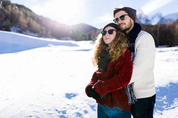 Beautiful young couple in love over winter background. - Stock Photo - Images