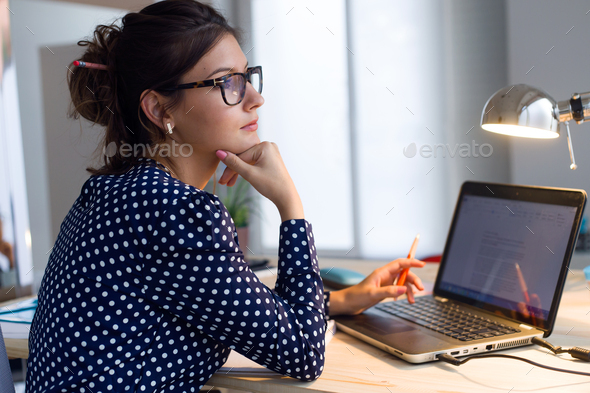 Beautiful young woman working with laptop in her office. - Stock Photo - Images
