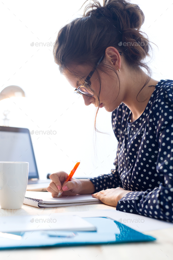 Beautiful young woman working in her office. - Stock Photo - Images