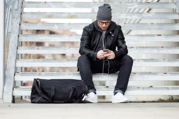 Modern young man using his mobile phone in the street. - Stock Photo - Images