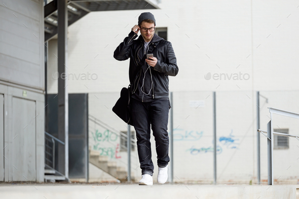 Modern young man listening to music with mobile phone in the str - Stock Photo - Images