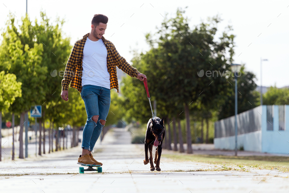 Handsome young man with his dog skateboarding in the park. - Stock Photo - Images
