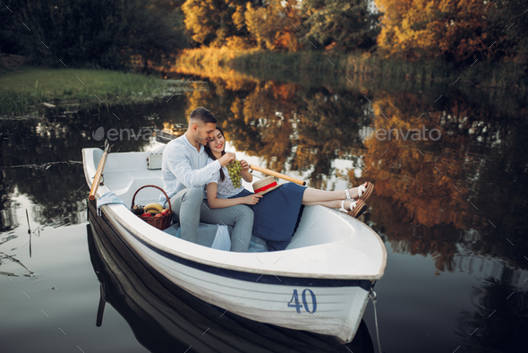 Love couple with fruit basket lying in a boat - Stock Photo - Images