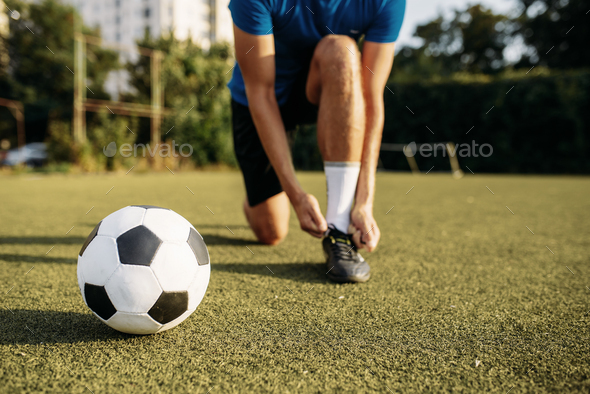 Male soccer player ties his shoelaces on boots - Stock Photo - Images