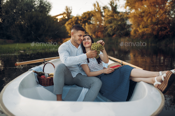 Love couple hugs in a boat on quiet lake - Stock Photo - Images