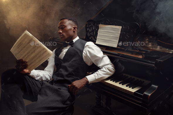 Black pianist with music notebook, jazz musician - Stock Photo - Images